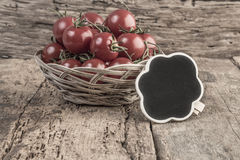 Chalkboard on ripe tomatoes on wooden table Royalty Free Stock Image