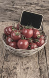 Chalkboard on ripe tomatoes on wooden table Stock Images