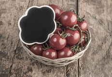 Chalkboard on ripe tomatoes on wooden table Royalty Free Stock Photos