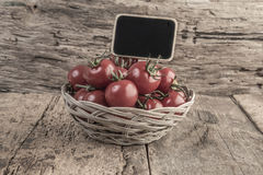 Chalkboard on ripe tomatoes on wooden table Stock Photography
