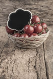 Chalkboard on ripe tomatoes on wooden table Royalty Free Stock Photography