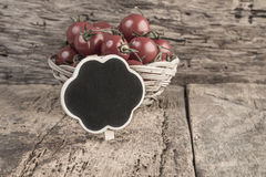 Chalkboard and ripe tomatoes on wooden table Royalty Free Stock Photo