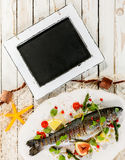 Chalkboard on Rustic Table with Whole Grilled Fish Royalty Free Stock Image