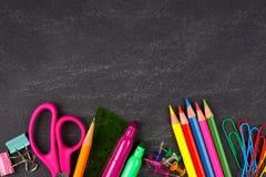 Chalkboard with school supplies bottom border stock photography