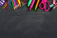 Chalkboard with school supplies top border. School supplies top border on a chalkboard background stock image