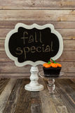 Chalkboard sign and pumpkin muffin on glass stand Stock Image