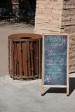 Chalkboard specials. A chalkboard sign with handwritten letters for a restuarant menu. A rusted garbage can is next to the sign and a stone pillar. Taken in Stock Photography