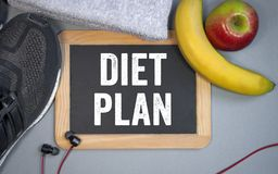 Chalkboard with sport shoes, fruits, towel and diet plan royalty free stock photo