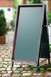 Chalkboard stand outside the restaurant Stock Images