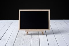 The chalkboard on the stand on wooden floor and black background stock image