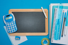 Chalkboard and stationery on blue background Royalty Free Stock Image