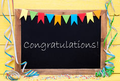 Chalkboard With Streamer, Text Congratulations. Blackboard With English Text Congratulations. Party Decoration Like Streamer And Confetti. Yellow Wooden Royalty Free Stock Images