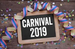 Chalkboard with streamers, confetti on wooden background with carnival 2019 royalty free illustration
