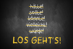 Chalkboard with stroked words like could and should and `Let`s go` in German Stock Photography