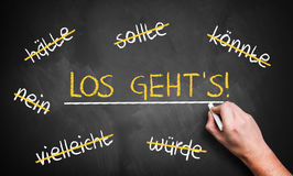 Chalkboard with stroked words like could and should and `Let`s go` in the middle. In German Royalty Free Stock Photos