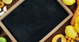 Chalkboard surrounded with fresh vegetables and fruits stock video footage