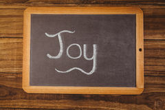 Chalkboard on table with joy text Royalty Free Stock Photos