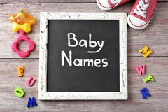 Chalkboard with text BABY NAMES. On wooden background stock photography