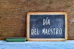 Dia del maestro, teachers day in Spanish. A chalkboard with the text dia del maestro, teachers day written in Spanish, and an eraser on a rustic wooden table stock images