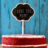 Chalkboard with the text I lovey you mom on a cake. Closeup of a red velvet cake topped with a chalkboard in the shape of a thought bubble with the text I lovey Stock Photography