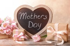 Chalkboard with text MOTHER`S DAY, tulips. And gift boxes on table stock photos