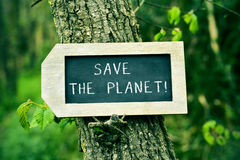 Chalkboard with the text save the planet in a tree Royalty Free Stock Photos
