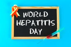 Chalkboard with text World Hepatitis Day. June 28th. Red yellow tape and syringe with blood on a blue background. Chalkboard with text World Hepatitis Day. June royalty free stock photos