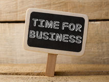 Chalkboard with Time For Business word on wooden background. Royalty Free Stock Photography