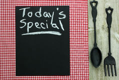 Chalkboard with Today's Special and cast iron spoon and fork. Today's Special on chalkboard with red checkered (gingham) tablecloth and cast iron spoon and fork Stock Image