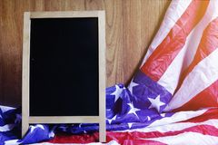 Chalkboard and USA Flag on Brown Wooden Wall Scene. Chalkboard and USA Flag on Brown Wooden Wall America Flag Background with Copy Space for MLK Day, President`s Royalty Free Stock Photo