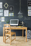 Chalkboard wall with optimistic phrases. Wooden computer desk and chair by a chalkboard wall with optimistic phrases Royalty Free Stock Image
