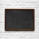 Chalkboard on white brick wall stock image