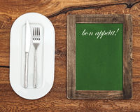 Chalkboard with white plate, knife and fork Royalty Free Stock Photos