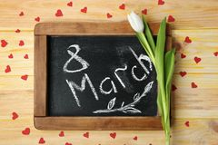 Chalkboard and white tulip on wooden background. Composition for International Women's Day stock images