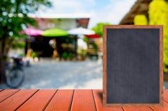 Chalkboard wood frame blackboard sign menu on wooden table. Stock Photography