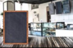 Chalkboard wood frame blackboard sign menu on wooden table, Blurred image background. Stock Images