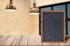 Chalkboard wood frame blackboard sign menu on wooden table, Blurred image background. Stock Image