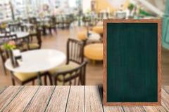 Chalkboard wood frame blackboard sign menu on wooden table. Stock Photos