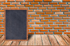 Chalkboard wood frame, blackboard sign menu on wooden table and brick wall background. Stock Photo