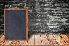 Chalkboard wood frame, blackboard sign menu on wooden table and brick wall background. Stock Photos
