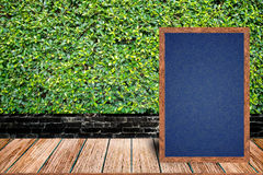 Chalkboard wood frame, blackboard sign menu on wooden table and grass wall background. Stock Photography