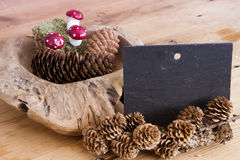 Chalkboard and wooden bowl with pinecones Royalty Free Stock Images