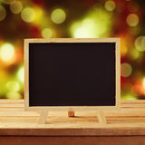 Chalkboard on wooden table over Christmas background Stock Photos
