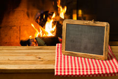 Chalkboard on wooden table over fireplace background. Winter and Christmas holiday Stock Photography