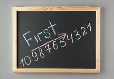 Chalkboard with word FIRST and numbers on grey background, top view. Victory concept stock photos