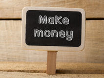 Chalkboard with  word Make money on wood background Stock Image