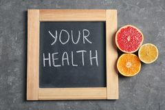 Chalkboard with words YOUR HEALTH and fruits on grey background, top view. Weight loss concept stock images