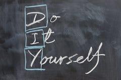 Chalkboard writing - DIY. Chalkboard writing - concept of DIY, do it yourself Stock Image