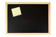 Chalkboard with yellow note. A empty black chalkboard with yellow note. Isolated on white background Stock Images
