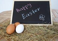 Chalkboard z tekst Szczęśliwą wielkanocą i naturalnymi jajkami Zdjęcia Royalty Free